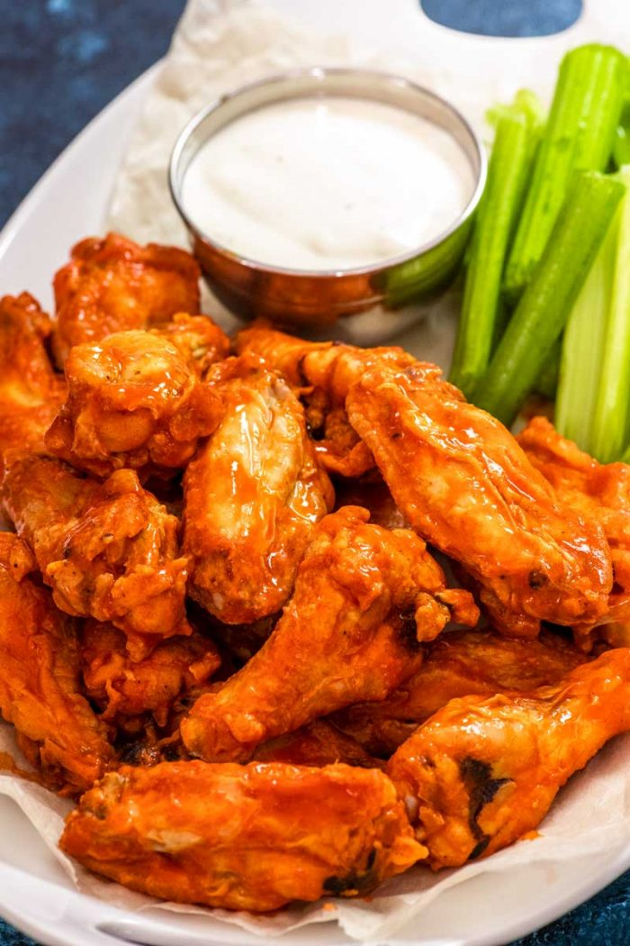 Buffalo Chicken Wings! Perfect for a party, these restaurant-style buffalo chicken wings are baked to crispy perfection (no deep frying!) and then coated in spicy buffalo sauce. | HomemadeHooplah.com