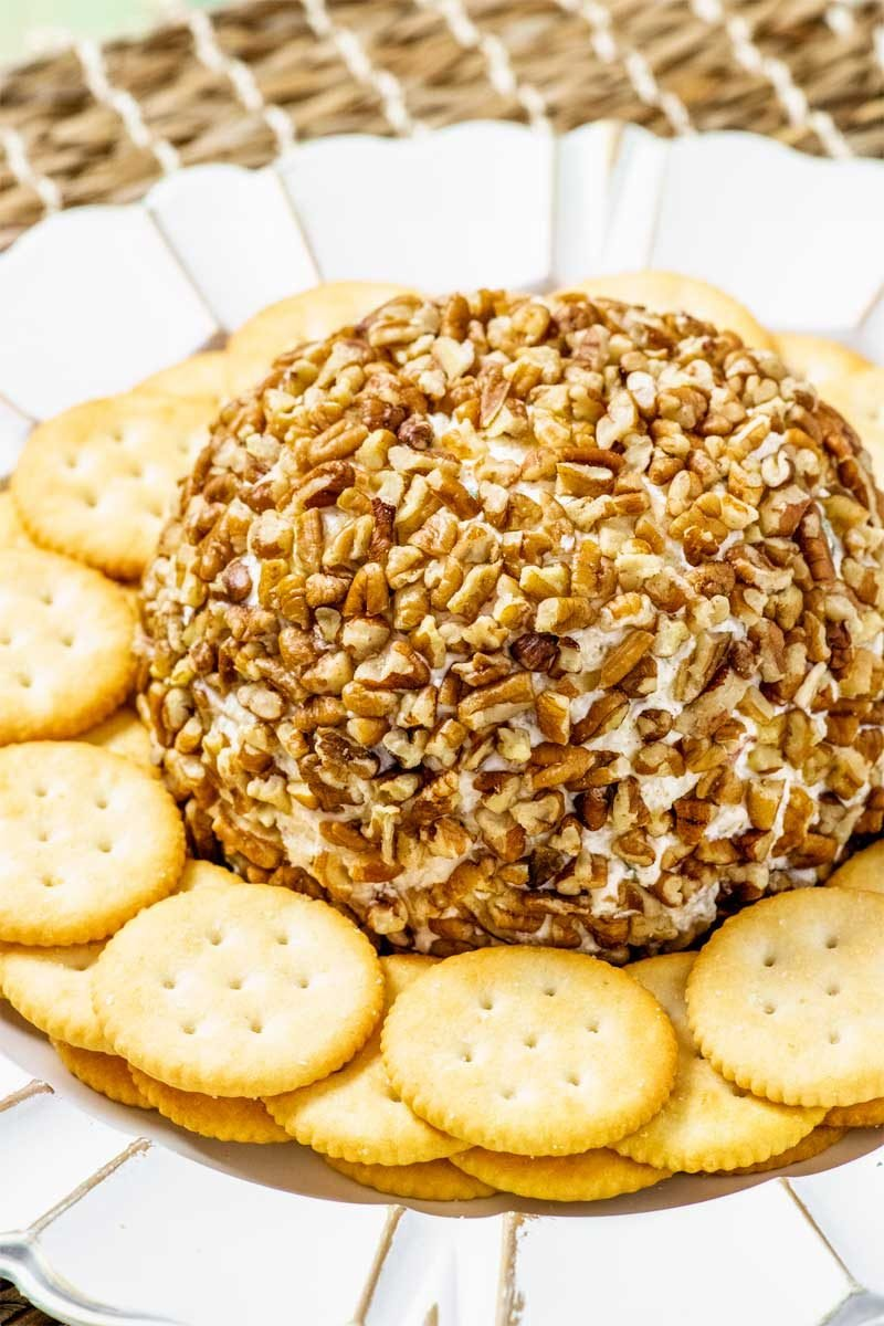 Pineapple cheese ball with pecans and red bell peppers.