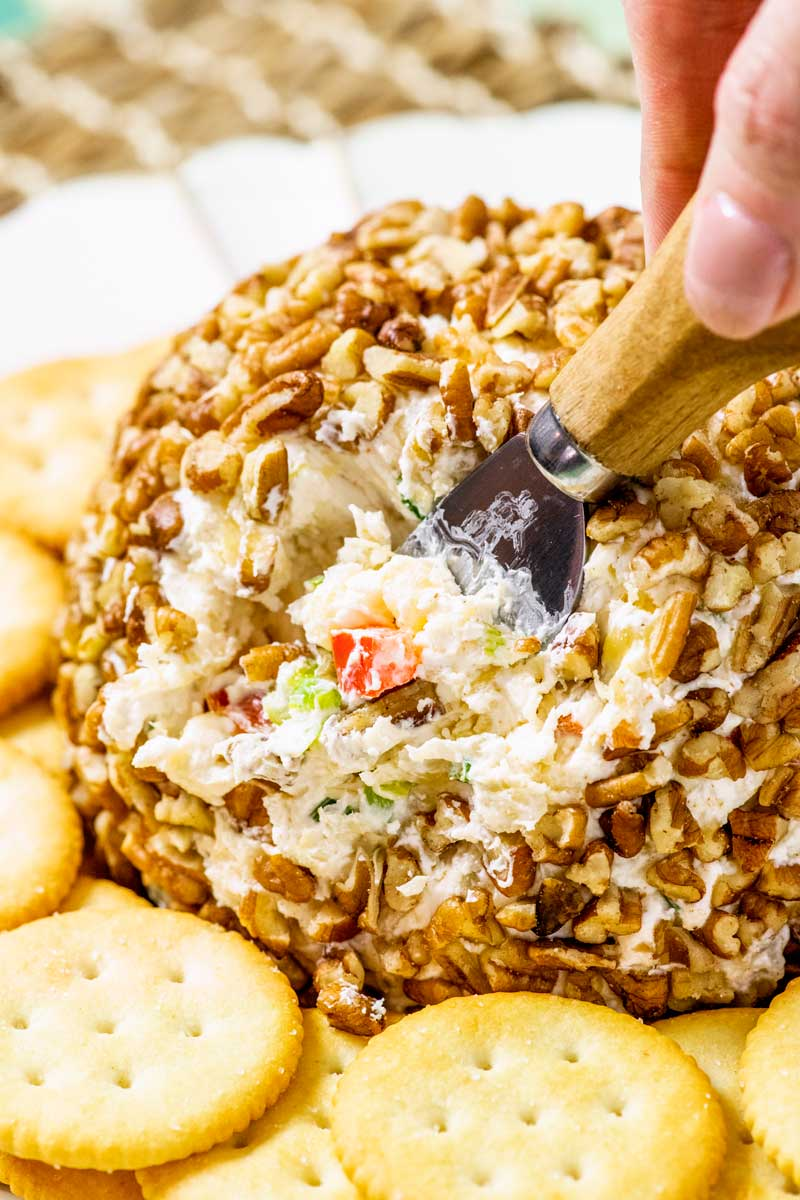 Pineapple Cheese Ball! This retro pineapple cheese ball is full of sweet and savory flavors like green onion, pineapple, red bell pepper, seasoned cream cheese, and chopped pecans. | HomemadeHooplah.com