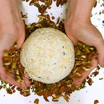 Bacon Ranch Cheese Ball Step 6 - Coat cheese ball with pecan mixture.