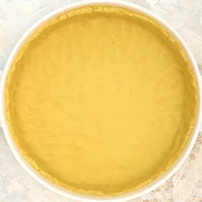 Glazed Fruit Pizza Step 2 - Place dough in a round pan and press to a flat layer, leaving a 3/4 lip around edge.