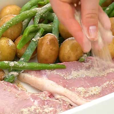 Sheet Pan Pork Chops with Vegetables Step 4 - Season everything with smoky ranch and minced garlic.