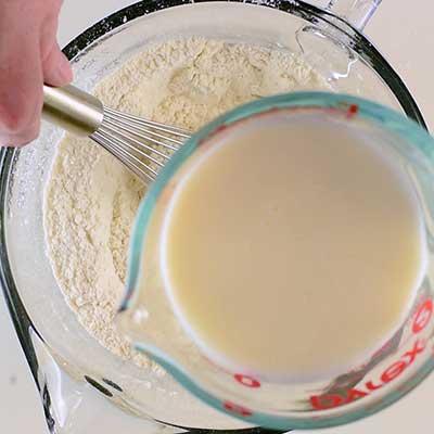 Traditional Irish Soda Bread Step 2 - Pour in some buttermilk.