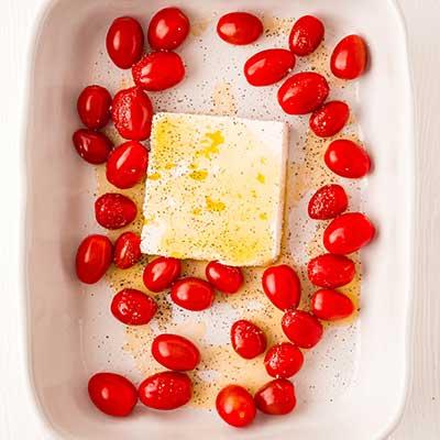 Massa Feta Assada Passo 1 - Adicione o queijo feta, o tomate, o azeite, o sal e a pimenta a uma assadeira.