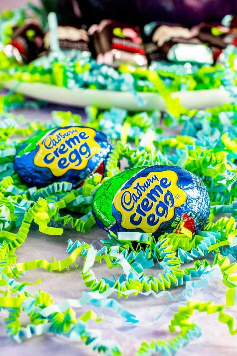 Cadbury creme egg candies resting on decorative paper.