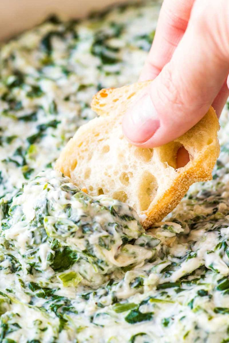 Dipping French bread into baked spinach dip.