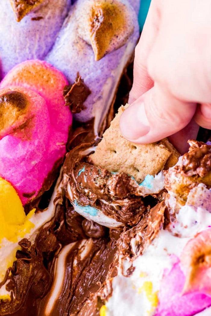 Mergulhando biscoitos de graham em camadas de Peeps e chocolate.