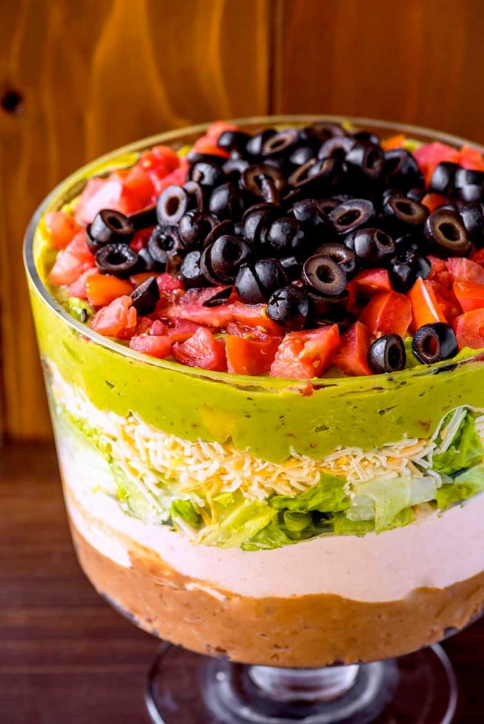 Layered dip with refried beans, sour cream, cheese, and veggies.