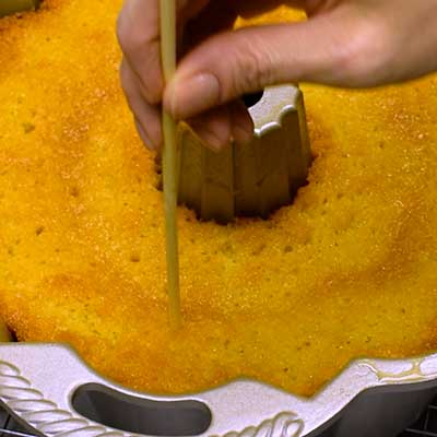 Kentucky Butter Cake Step 7 - Use a skewer to poke holes in bottom of cake.