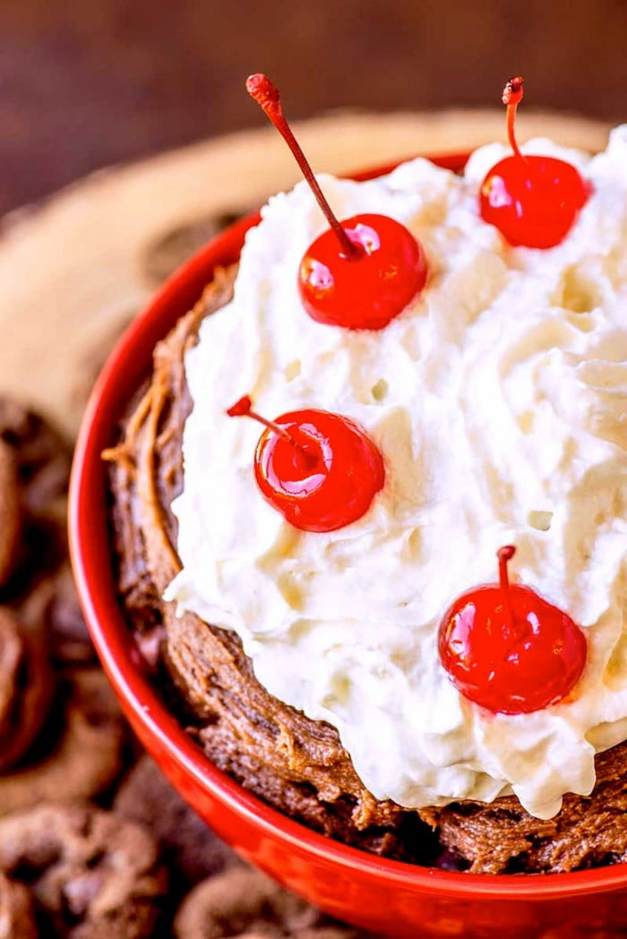 Cherries and cream on top of chocolate dip.
