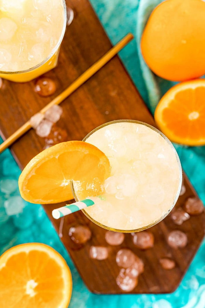 Screwdrivers served with ice, straws, and an orange slice.