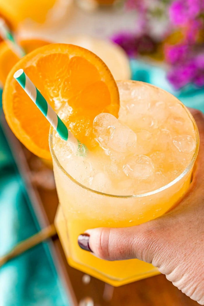Holding a screwdriver cocktail mixed with vodka, orange juice, salt, and club soda.