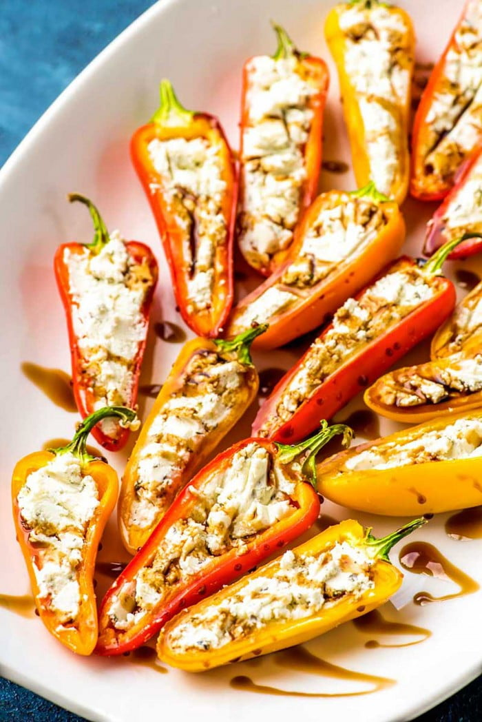 Mini peppers stuffed with goat cheese and drizzled with balsamic reduction.