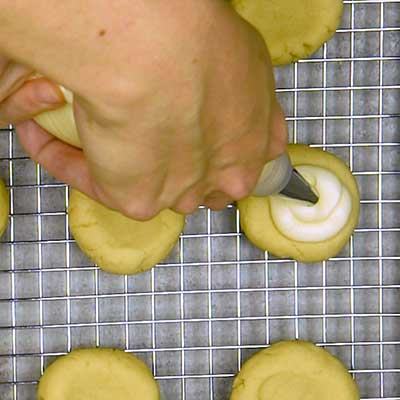 Patriotic Fruit Pizza Cookies Step 7 - Fill well in cookies with vanilla frosting.