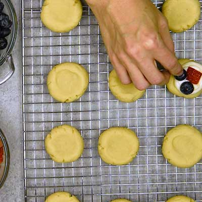 Patriotic Fruit Pizza Cookies Step 7 - Place fruit on top of the frosting.