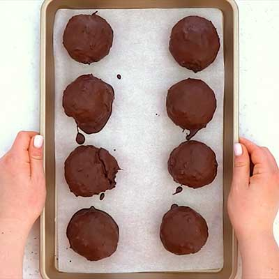 Peanut Butter Brownie Bombs Step 6 - Place coated brownie bombs on a baking sheet to harden.