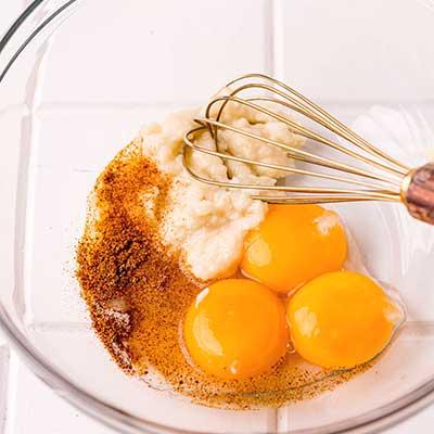 Aioli Sauce Step 1 - Add egg yolks, garlic paste, water, salt, and cayenne pepper to bowl.