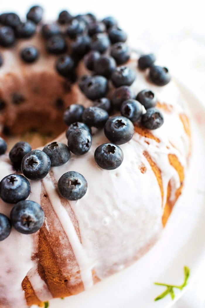 Sour cream blueberry bundt cake with glaze and blueberries on top.