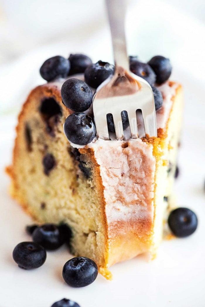 Fork piercing a slice of sour cream bundt cake.