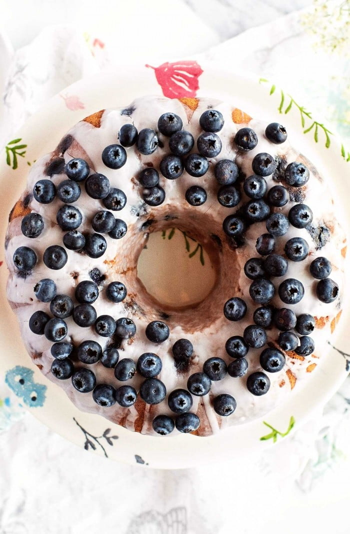 Top down view of bundt cake decorated with sugar glaze and blueberries.