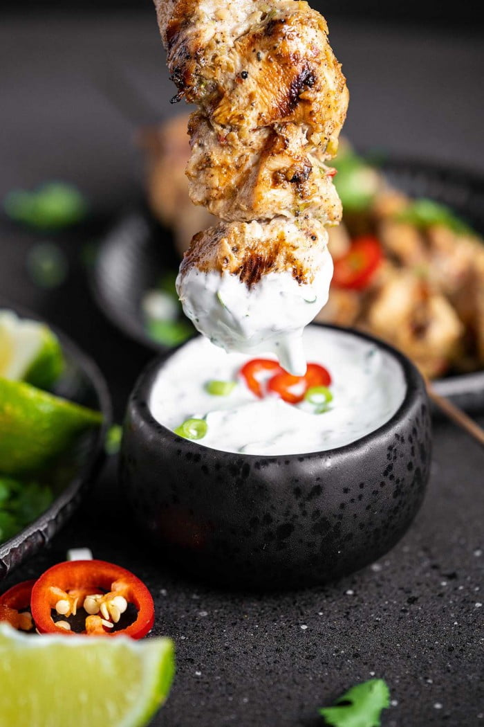 Dipping a chicken skewer in cilantro lime ranch.