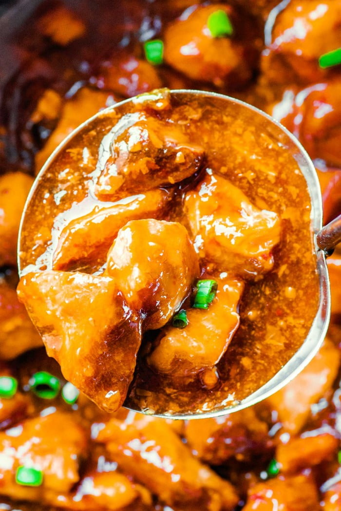 Spoon holding bourbon chicken.