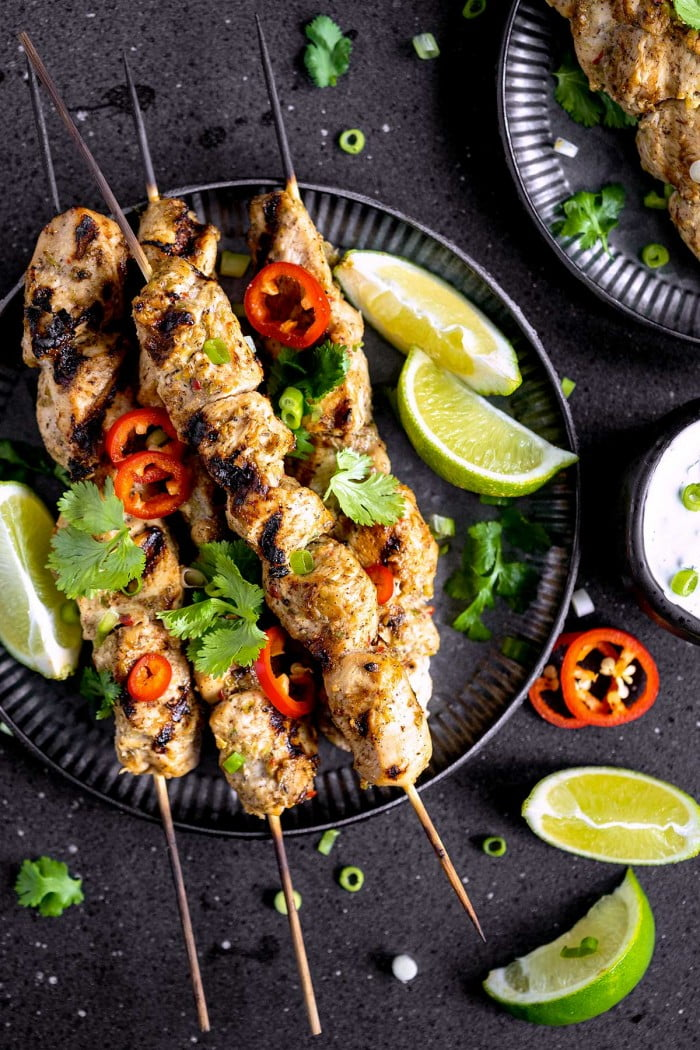 Top down view of jerk chicken skewers on a plate with garnishes.