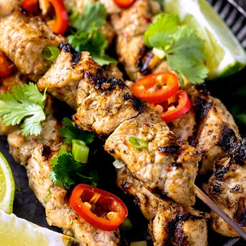 Closeup of jerk chicken skewers on a plate.