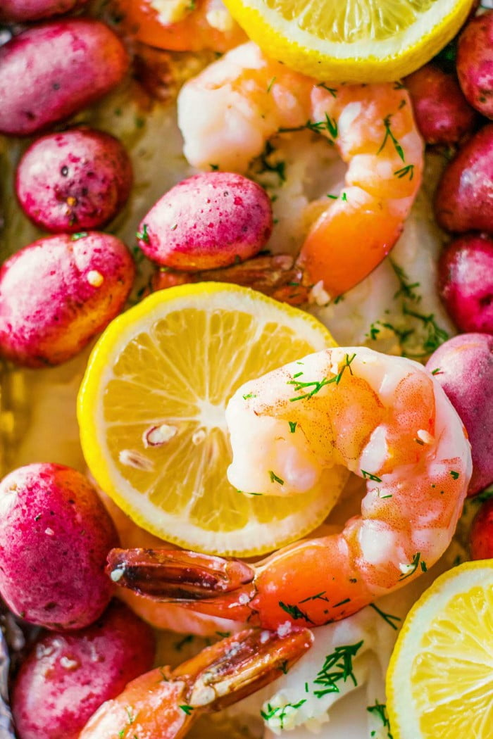 Seafood boil with shrimp, fish, red potatoes, and corn.