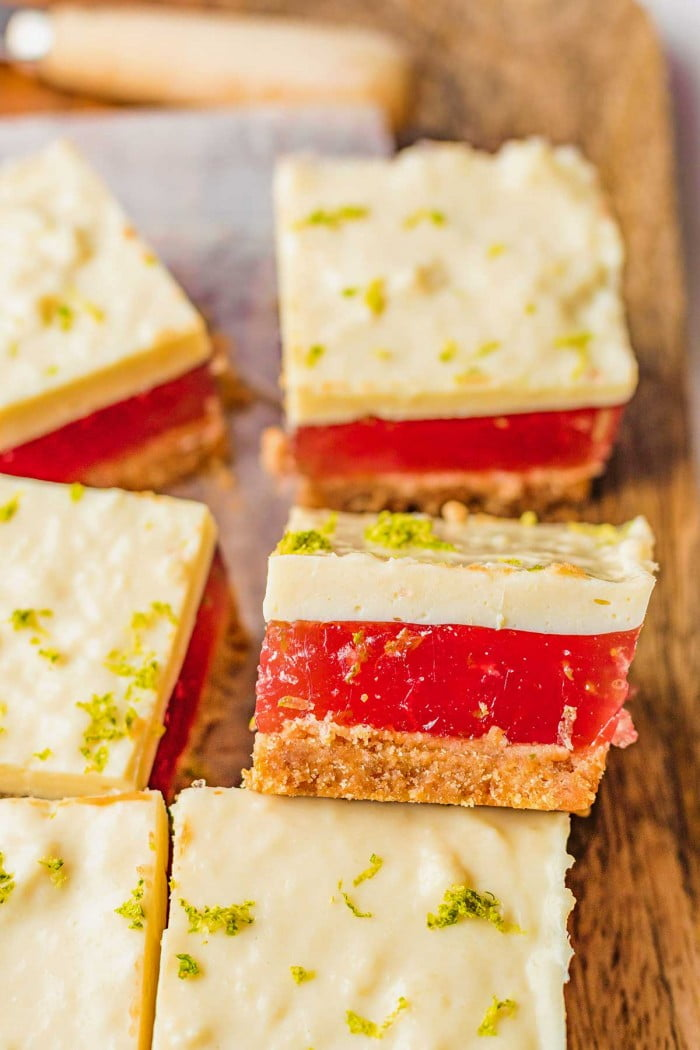Rows of creamy lime bars with a watermelon layer.