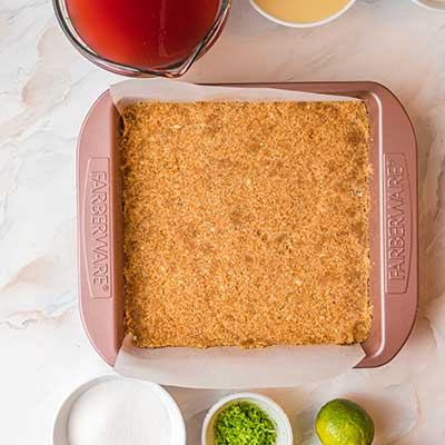 Watermelon Tequila Lime Bars Step 1 - Add crust mixture to a baking dish and press firmly.