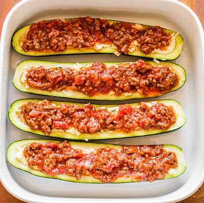 Lasagna Zucchini Boats Step 3 - Top the cheese layer with a mixture of cooked ground beef and red sauce.