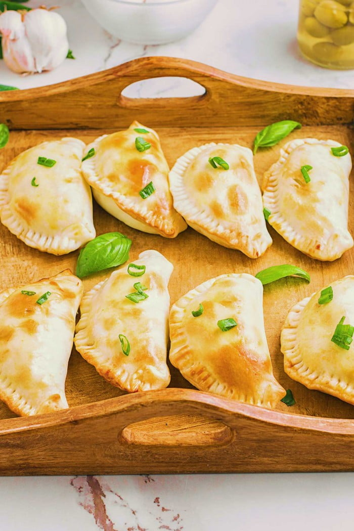 Beef empanadas served on a wooden tray.