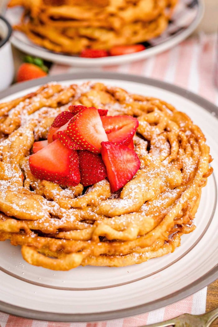 Close up of funnel cake served with fruit.