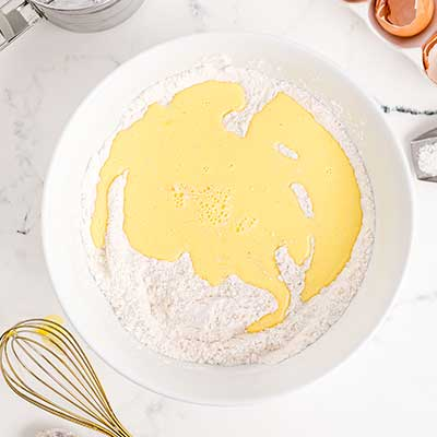 Homemade Funnel Cakes Step 3 - Add milk and eggs to bowl.