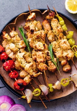 Grilled greek chicken skewers on a plate.