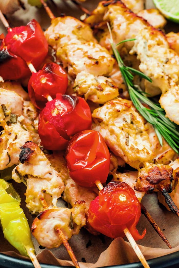 Close up tomatoes and greek chicken on skewers.