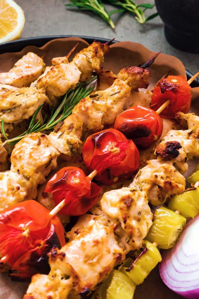 Close up of greek chicken skewers with rosemary garnish.