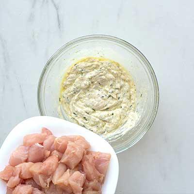 Greek Chicken Skewers Step 2 - Add chicken to bowl with marinade.