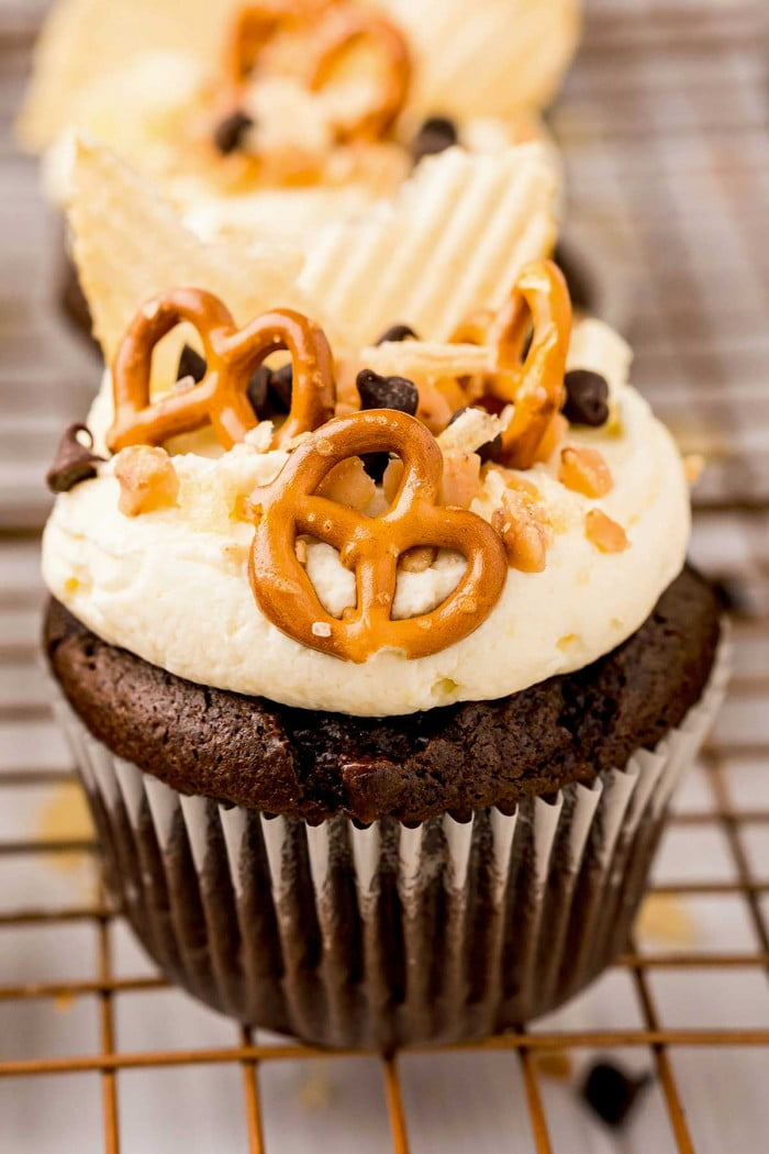 Close up of pretzels, potato chips, chocolate chips, and toffee bits topping a cupcake.