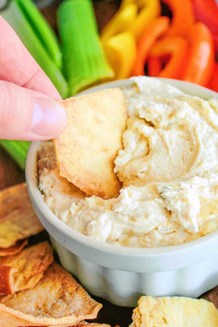 Dipping a chip in ranch hummus.
