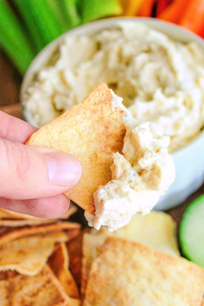 Holding a chip covered in ranch hummus.