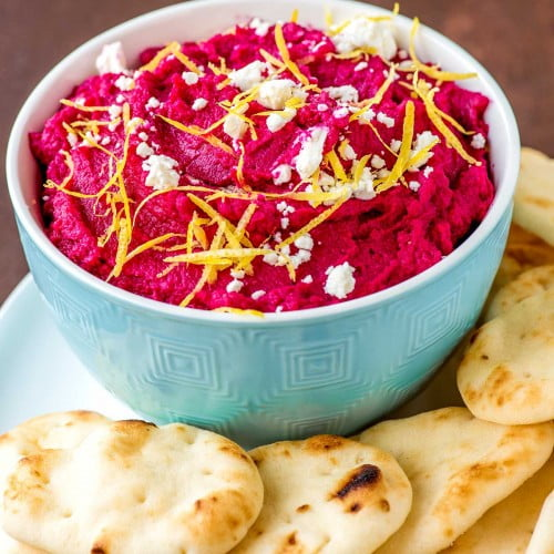 Vibrant roasted beet hummus served in a bowl with pita bread.