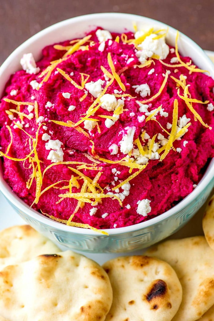 Close up of roasted beet hummus garnish with feta cheese and lemon zest.