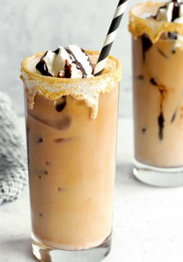 S'mores iced coffee in a tall glass with striped straw.