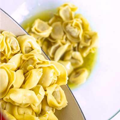 Tortellini Pasta Salad Step 3 - Add pasta to bowl with dressing.