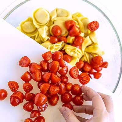 Tortellini Pasta Salad Step 3 - Add cherry tomatoes.