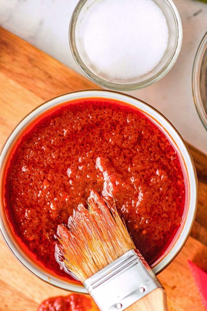 Basting brush dipping into watermelon bbq sauce.