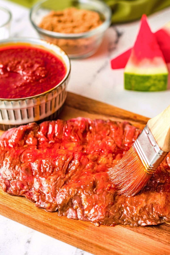 Brushing cooked beef with watermelon bbq sauce.