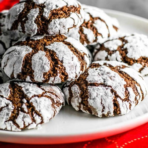 Baked chocolate crinkle cookies stacked on a plate.